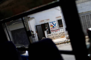A graffiti reading 'We go for you, Los Colectivos' is seen outside a building of 'Manos para Vargas' foundation, lead by opposition lawmaker Jose Olivares in La Guaira, Caracas