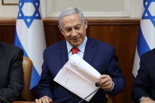 Israeli Prime Minister Benjamin Netanyahu holds a paper at the start of the weekly cabinet meeting at his Jerusalem office