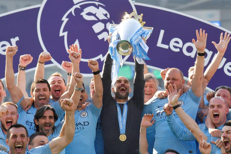 Pep Guardiola levanta o troféu da Premier League de 2019 ao lado dos jogadores