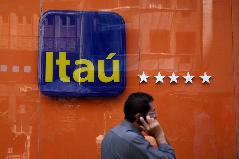 Um homem falando ao celular passa andando na frente de uma agência do Itaú no Rio de Janeiro.