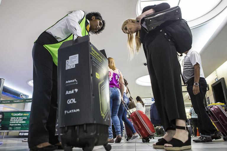 Passageira observa enquanto fiscal da Abear mede sua mala de mão no aeroporto de Congonhas (SP)