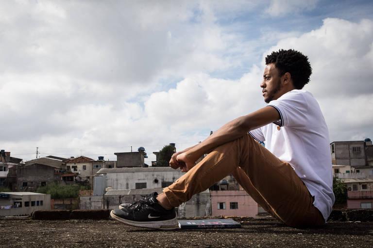 De camiseta branca, bermuda e perfil, o estudante Tiago, negro e jovem, é fotografado de perfil sentado sobre uma laje, com o céu e as casas do bairro onde vive ao fundo