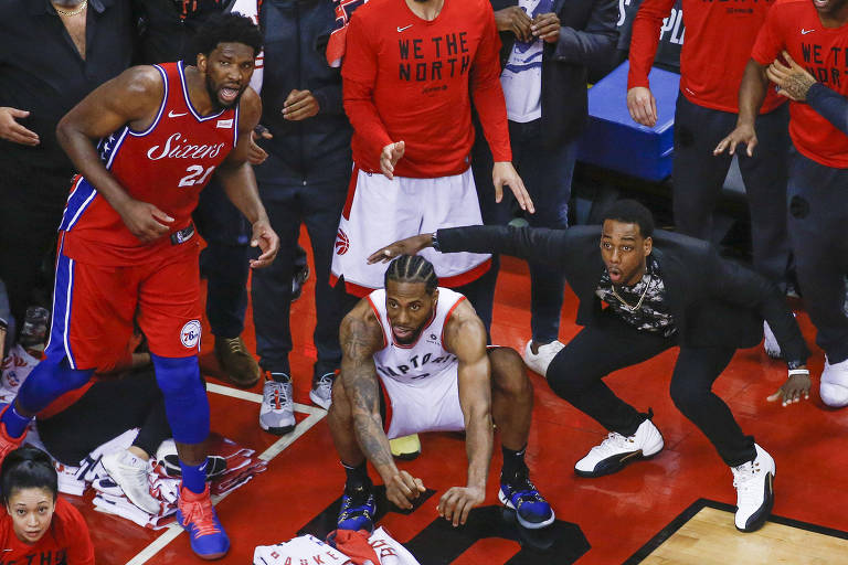 Joel Embiid, do Philadelphia 76ers, e Kawhi Leonard e Jordan Loyd, do Toronto Raptors, em lance decisivo da NBA