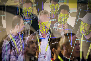 Attendees interact with a facial recognition demonstration during the Consumer Electronics Show in Las Vegas.