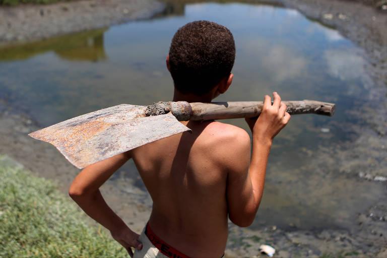 Criança trabalha próxima ao rio Capibaribe, em Recife