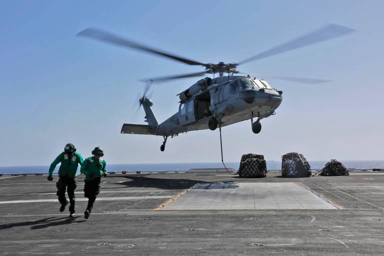 Especialistas em logística naval próximo a um helicóptero Sea Hawk MH-60S