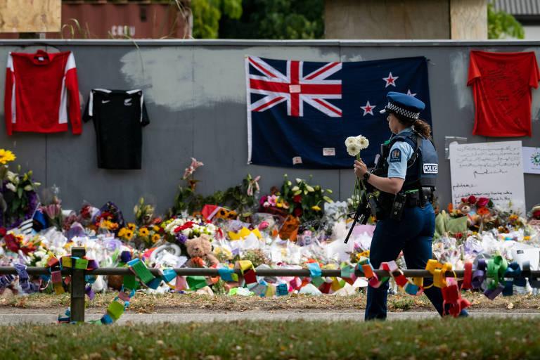 Policial com flores durante cerimônia em homenagem às vítimas do massacre em Christchurch, na Nova Zelândia