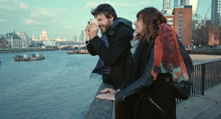 O jovem Rafael (Rafael de Bona) segura uma câmera ao lado de uma garota, em uma cidade da Europa