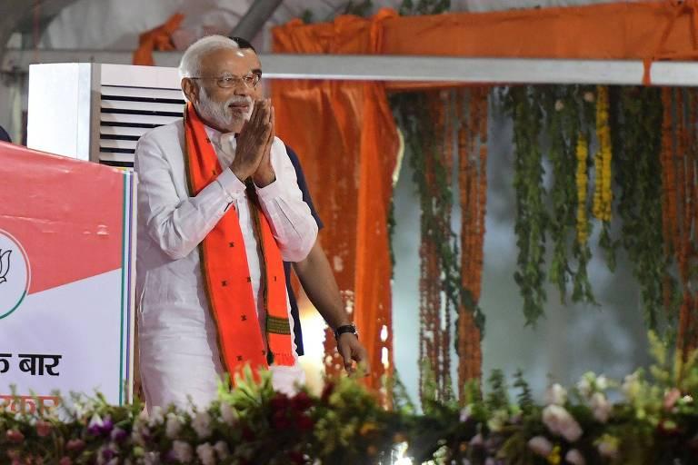 Modi faz gesto com as duas mãos unidas na frente do peito em cima de palco decorado com faixas cor de laranja