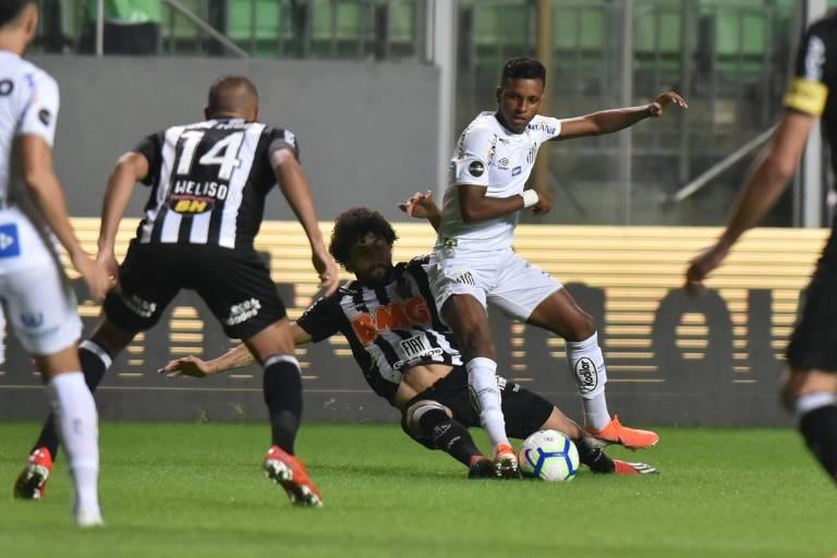 O santista Rodrygo tenta escapar da forte marcação do atleticano Luan; o empate sem gols em Belo Horizonte adiou a definição da vaga nas quartas de final