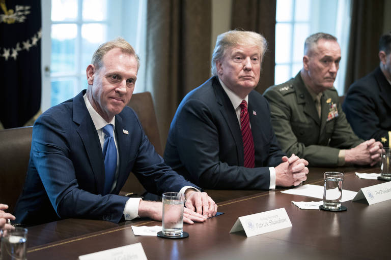 FILE -- President Donald Trump is flanked by Acting Defense Secretary Patrick Shanahan, left, and Gen. Joseph Dunford, the chairman of the Joint Chiefs of Staff, at the White House on April 3, 2019. Trump has told Shanahan that he does not want to go to war with Iran, according to several administration officials. (Sarah Silbiger/The New York Times)