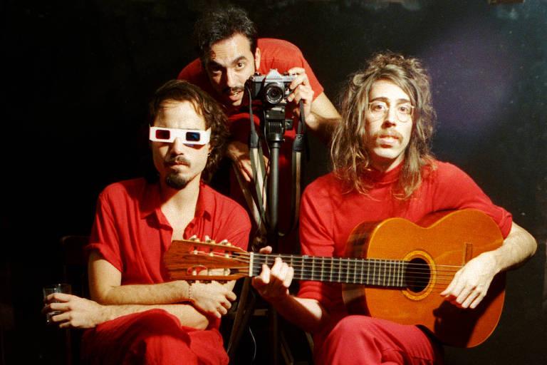 Três homens de vermelho; um com violão, outro com uma câmera e outro com óculos 3-D