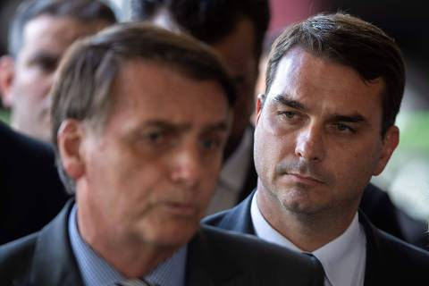 (FILES) In this file photo taken on November 28, 2018, The president-elect of Brazil, Jair Bolsonaro (L) and his son Flavio Bolsonaro (R), arrive for a press conference on the appointment of the ministers of Citizenship, Tourism and Regional Development at the headquarters of the transitional government in Brasilia on November 28, 2018. - The eldest son of Brazilian President Jair Bolsonaro has denied accusations he laundered money through real estate deals, months after the eruption of a suspicious payments scandal involving him that tarnished his father's anti-corruption credentials. (Photo by Sergio LIMA / AFP) ORG XMIT: SLI