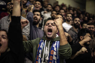 Fans react during a professional basketball game in Dik El Mehdi, Lebanon, where passion for the sport is strong.