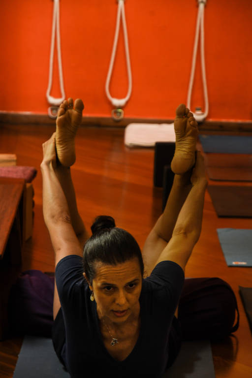 Mulher deitada de barriga para baixo, com tronco levantado, segura os dois pés por trás do corpo