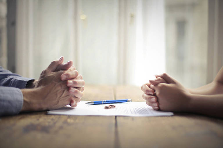 Imagem ilustrativa de casal com papéis de divórcio