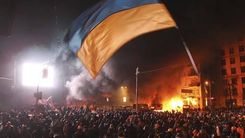 Protesto contra o governo reúne 200 mil pessoas, em Kiev (Ucrânia). Apesar da lei proibir manifestações. A marcha foi pacífica por três horas mas acabou em confronto, com policiais e civis feridos e veículos queimados. *** Pro-European protesters gather around burning vehicles during clashes with Ukrainian riot police in Kiev January 19, 2014. Protesters clashed with riot police in the Ukrainian capital on Sunday after tough anti-protest legislation, which the political opposition says paves the way for a police state, was rushed through parliament last week.  REUTERS/Valentyn Ogirenko (UKRAINE - Tags: POLITICS CIVIL UNREST CRIME LAW) ORG XMIT: KIE83