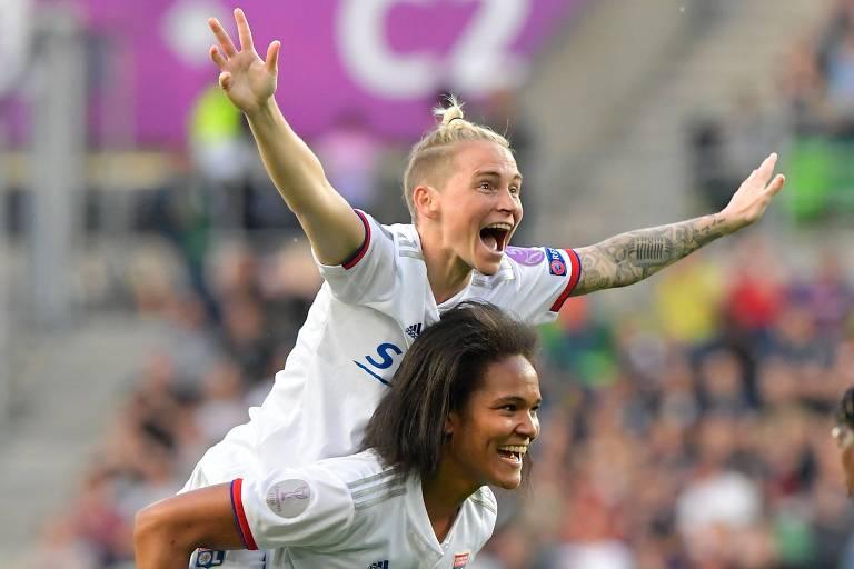 A meia galesa Jess Fishlock sobe nas costas da zagueira francesa Wendie Renard para comemorar a vitória do Lyon na final da Champions League feminina