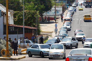 People with their vehicles wait in line to refuel at a gas station of the state oil company PDVSA in Maracaibo
