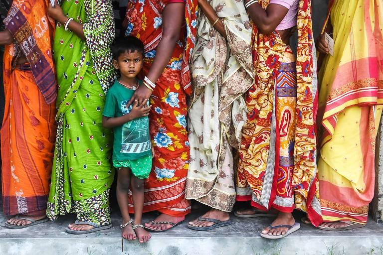 criança em meio a fila de adultos com roupas coloridas