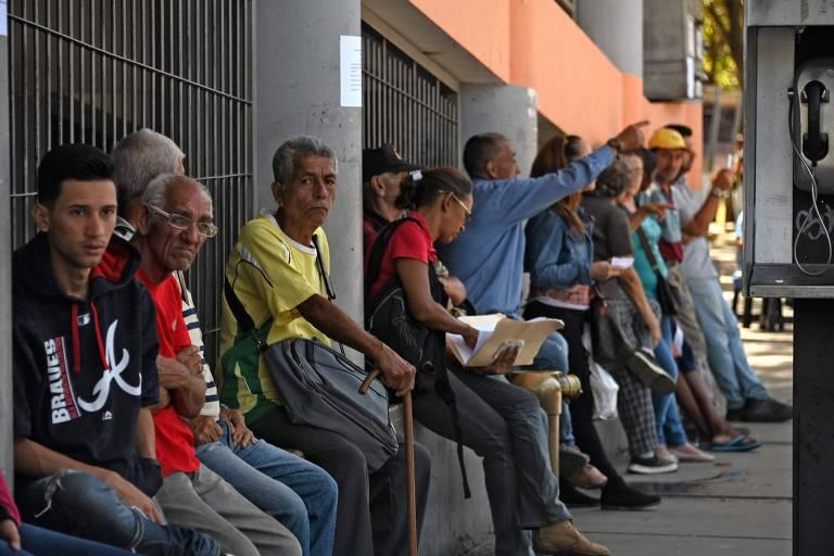 fila de homens sentados na rua