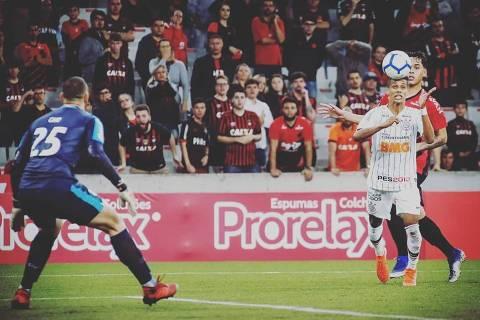 Pedrinho toca de cabeça por cima do goleiro Caio, do Athletico-PR, para marcar o segundo gol corintiano na Arena da Baixada, em Curitiba (PR)