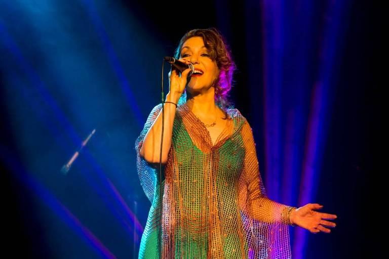 Cantora Vânia Bastos canta ao microfone durante apresentação ao vivo
