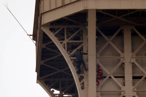 An unidentified man climbs the Eiffel Tower, which had to be evacuated, next to a Paris fire brigade specialist in Paris, France, May 20, 2019. REUTERS/Charles Platiau ORG XMIT: EIF003
