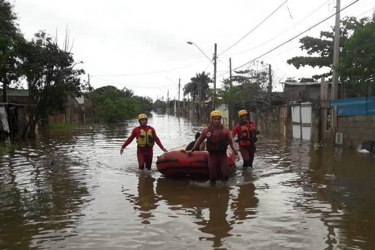 Quatro pessoas vestidas com uniforme dos Bombeiros, em vermelho, arrastam um bote com duas vítimas