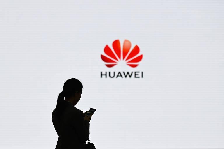 Mulher segura smartphone em frente ao logo da Huawei