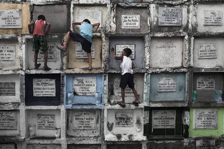 Meninos escalam lápides de um cemitério em Manila, capital das Filipinas; clique de Gustavo Gusmão integra 'Limbus', sua individual no MIS