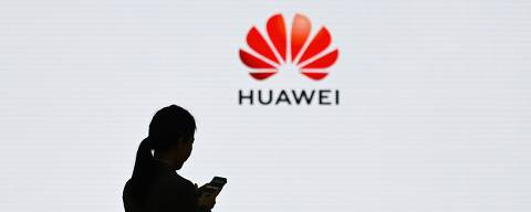 (FILES) In this file photo taken on March 6, 2019 a staff member of Huawei uses her mobile phone at the Huawei Digital Transformation Showcase in Shenzhen, China's Guangdong province. - US internet giant Google, whose Android mobile operating system powers most of the world's smartphones, said on May 19, 2019 it was beginning to cut ties with China's Huawei, which Washington considers a national security threat. (Photo by WANG ZHAO / AFP)