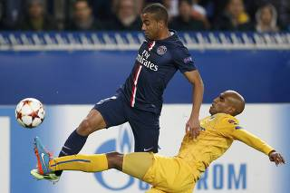 Paris St Germain's Lucas is challenged by APOEL Nicosia's Carlao during their Champions League soccer match at the Parc des Princes in Paris