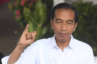 Indonesian President Joko Widodo shows his ink-stained finger after casting his ballots during elections in Jakarta