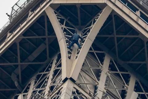 TOPSHOT - A man (C) climbs up to the top of the Eiffel Tower, in Paris, without any protection, on May 20, 2019. - The Eiffel Tower was evacuated on May 20, 2019 in the afternoon after a person was spotted climbing up the Paris landmark, the company that operates the structure said.