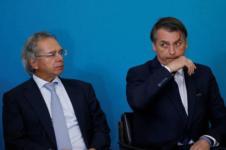 Paulo Guedes sentado à direita; Bolsonaro, também sentado, está ao lado esquerdo do ministro da Economia