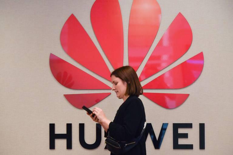Mulher caminha em frente a logo da Huawei