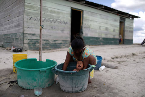 A Venezuelan indigenous woman of Pemon tribe baths her baby in the Brazilian indigenous village Tarau Paru in the border city of Pacaraima, Brazil April 14, 2019. Picture taken April 14, 2019. REUTERS/Pilar Olivares ORG XMIT: HFS-PON07