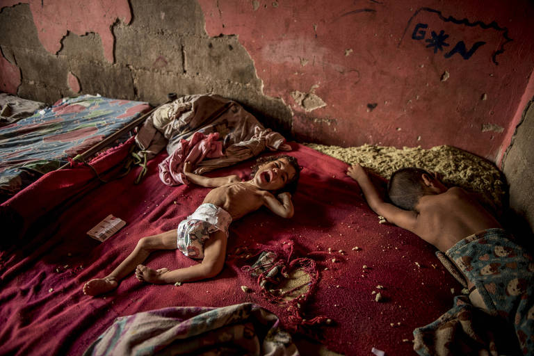 FILE-- Two-year-old Anailin, left, suffers from severe malnutrition and treatable muscular paralysis in a shack nearby the local hospital, which is empty ? its last patient died without care, in Toas Island, Venezuela, May 6, 2019. Her mother, Maibeli Nava, said doctors prescribe medications that are unavailable or unaffordable. Many who saw this picture of Anailin Nava wanted to help. One nurse packed some food and hitchhiked to her home. (Meridith Kohut/The New York Times)