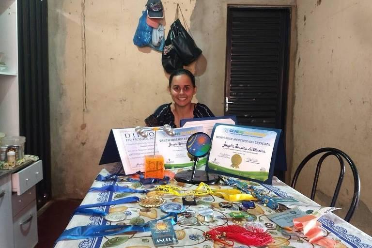 A ex-aluna de Joana D'Arc Félix, Ângela Ferreira de Oliveira, 22, na casa de sua família em Claraval, com prêmios e certificados de participação em feiras, concursos e congressos científicos