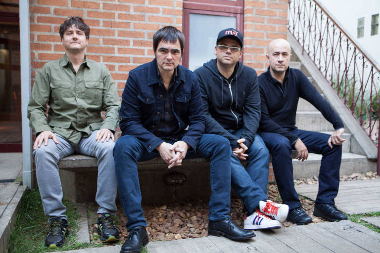 Sentados em um banco, os quatro integrantes do Skank (da esq. para a dir.) são Lelo Zaneti, Samuel Rosa, Henrique Portugal e Haroldo Ferretti