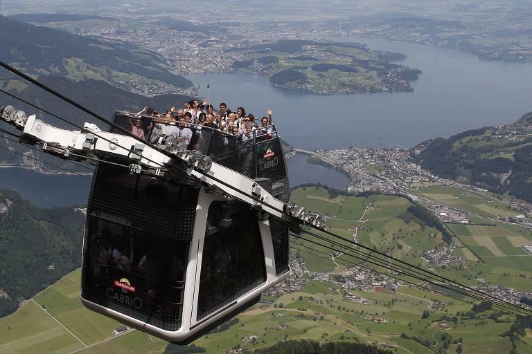 Pessoas em deque aberto de teleférico, com vista para lago