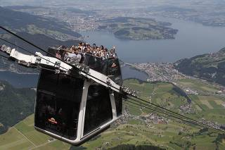 People wave during the inauguration trip of the world's first open-air doubledecker cable car system on the Stanserhorn mountain