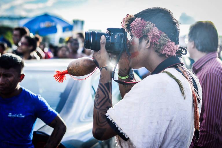 """Indígena com câmera fotográfica em cena do curta-metragem """"ATL - Acampamento Terra Livre"""""""