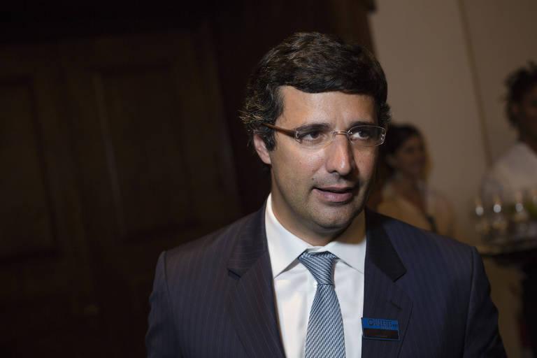 O banqueiro André Esteves, de terno escuro, camisa branca e gravata cinza