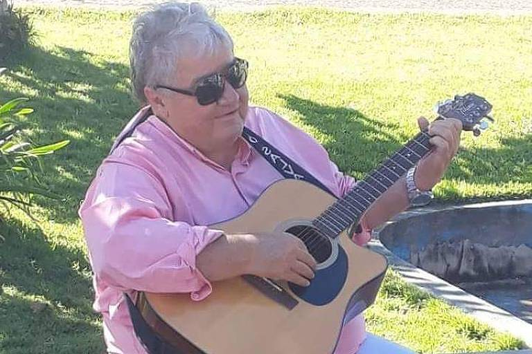 Cantor Nilton Lamas, vestindo calça jeans, camisa rosa, óculos escuros e sapatos pretos toca violão em um banco.