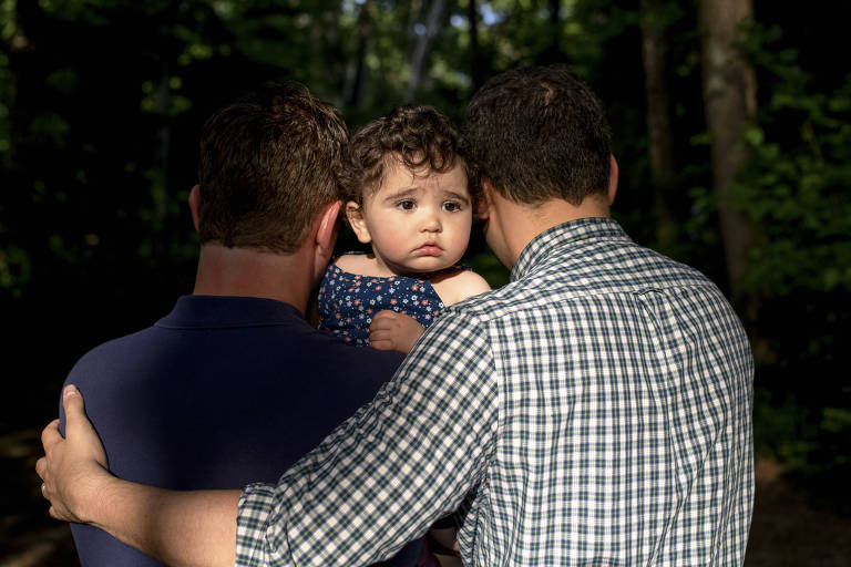 James Derek Mize, left, and his husband, Jonathan Gregg, with their infant daughter Simone, who was born in England to a surrogate mother, in Decatur, Ga., May 15, 2019. Under a decades-old policy that has come under increasing scrutiny, Simone does not qualify for citizenship at birth, even though both her parents are American. (Johnathon Kelso/The New York Times)