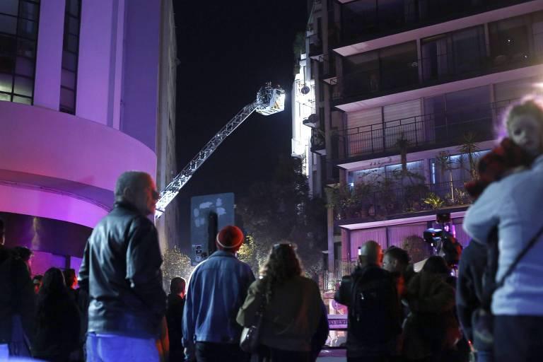 Público observa ação de bombeiros chilenos no prédio onde seis brasileiros morreram em Santiago