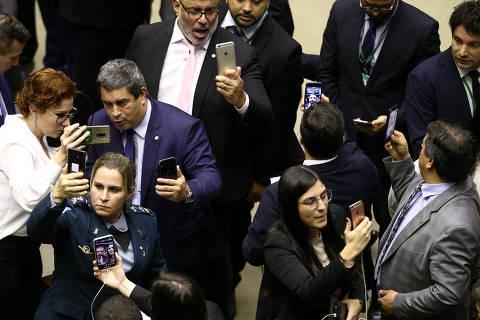 Qual legenda você dá para a imagem de deputados fazendo vídeos durante votação na Câmara?
