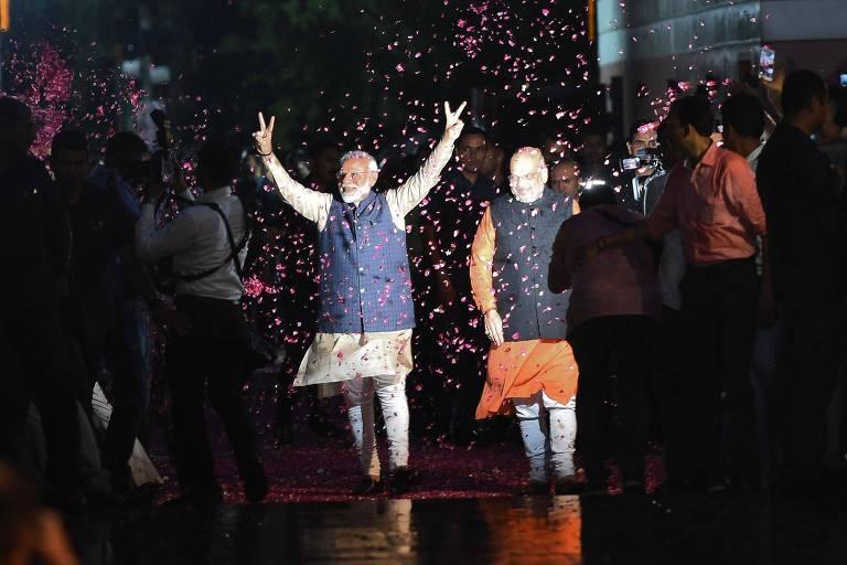 O premiê indiano Narendra Modi, com os braços levantados, após a vitória nas eleições
